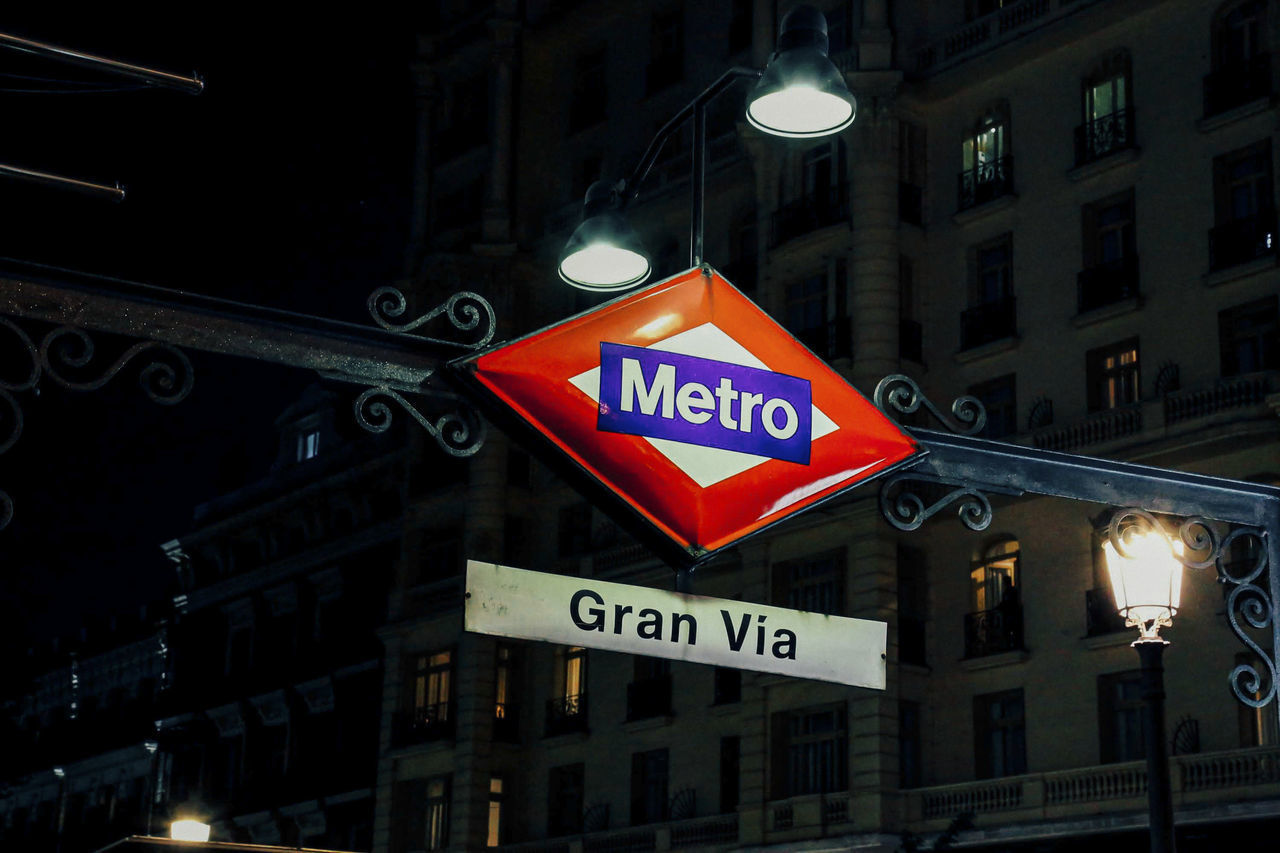 LOW ANGLE VIEW OF ROAD SIGN AGAINST ILLUMINATED BUILDING