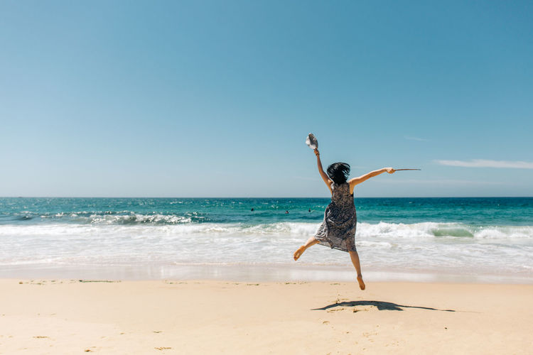 Beach Sea Land Sky Water Horizon Over Water Human Arm Horizon Full Length Leisure Activity One Person Motion Limb Clear Sky Sand Nature Arms Raised Beauty In Nature Lifestyles Arms Outstretched Freedom Outdoors Travel People Portrait