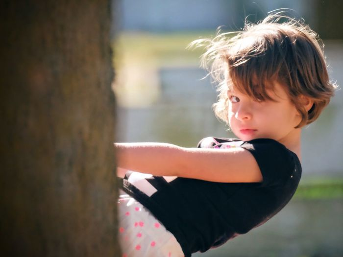 Portrait of cute girl playing while sitting in playground