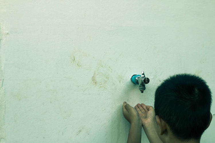 Close-Up Of Boy With Hands Cupped On Faucet Against Wall