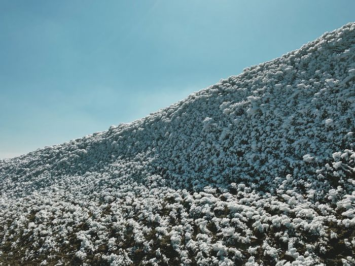 Low angle view of snow covered mountain against sky