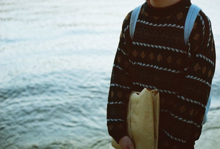 Midsection of man wearing sweater while standing against sea at beach
