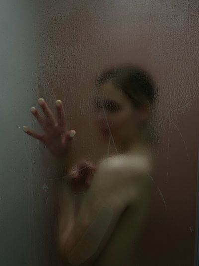 Naked young woman in bathroom seen through window