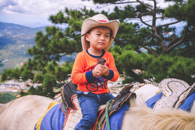 Boys Casual Clothing Child Childhood Cowboy Cowboy Hat Day Domestic Domestic Animals Focus On Foreground Front View Hat Innocence Leisure Activity Lifestyles Males  Mammal Men One Person Outdoors Pets Real People Riding