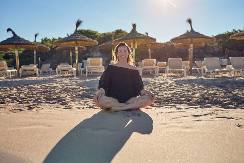 Smiling barefoot woman sitting on the beach Meditating Meditation Vacations Woman Yoga Yoga Pose Beach Best Ager Day Front View Full Length Happiness Leisure Activity Lifestyles Looking At Camera Middle-aged One Person Outdoors Real People Sand Sitting Smiling Spiritual Summer Sunlight