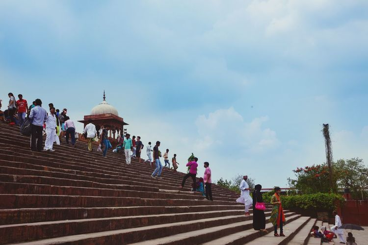 People walking on staircase against cloudy sky