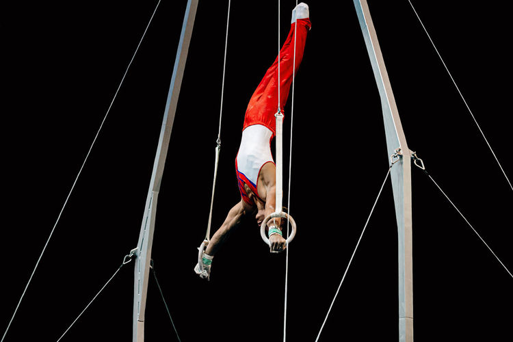 Low angle view of man performing acrobat against black background