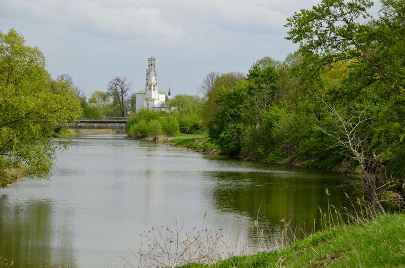 Scenic view of lake by temple against sky