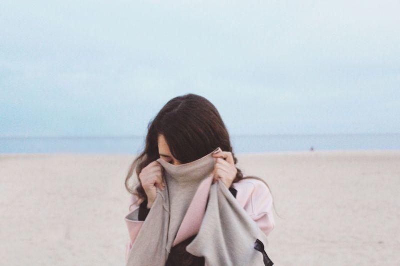 Woman Covering Face At Beach Against Sky