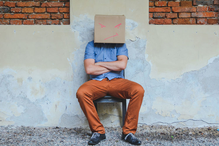 Man wearing cardboard box with attitude expression against wall