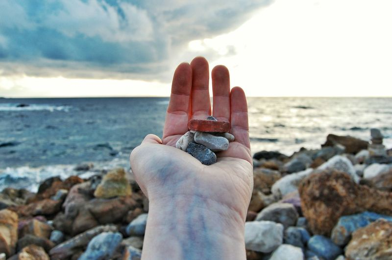 Close-up of hand holding rock at beach against sky
