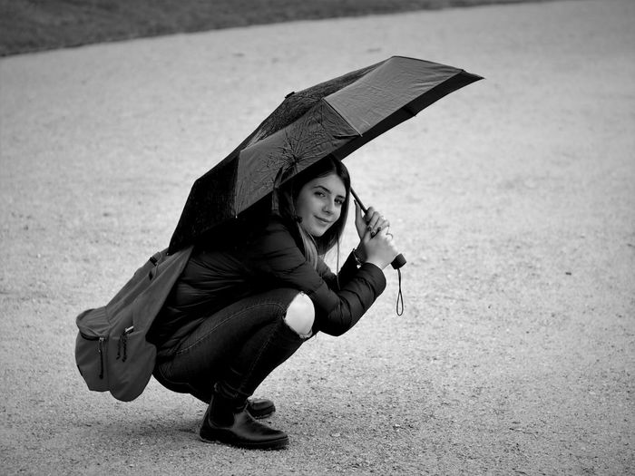 Portrait of young woman holding umbrella on land