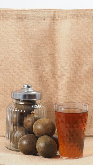 Close-up of drink in jar on table against wall