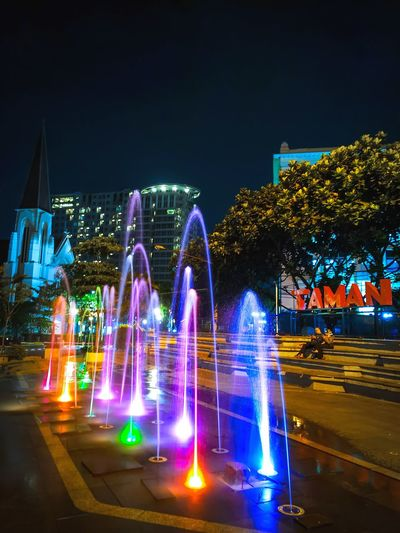 Illuminated fountain by building against sky at night