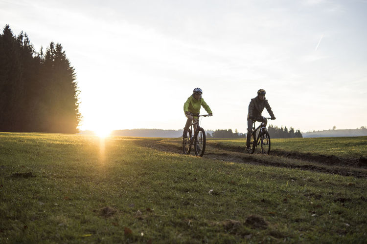 Men riding bicycle on grass against sky