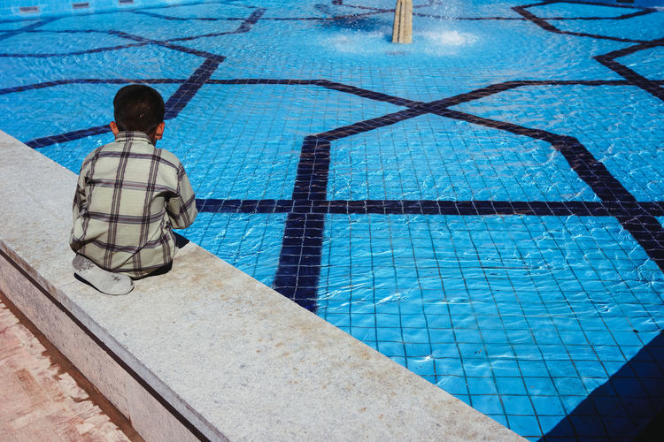 Rear view of boy on swimming pool