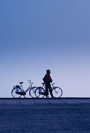 Man with bicycle against clear sky