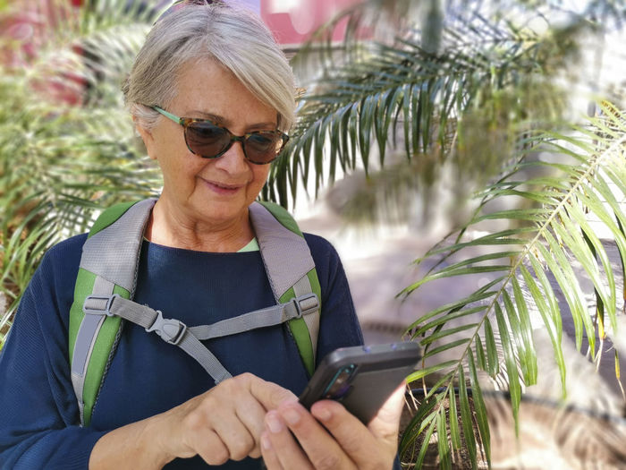 Smiling senior woman checking phone while standing by plant