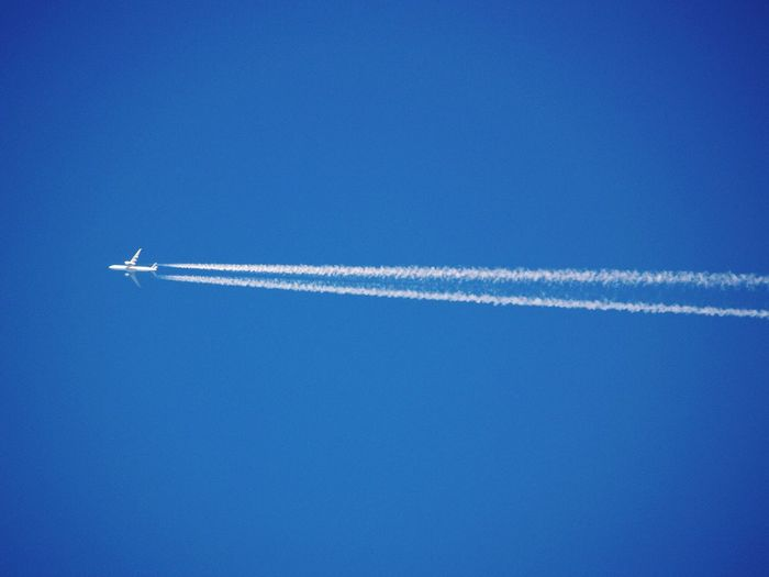 Low angle view of jet airplane flying in clear blue sky