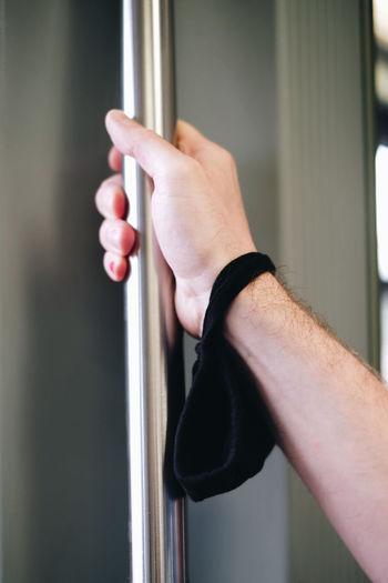 Close-up of hand holding metal door