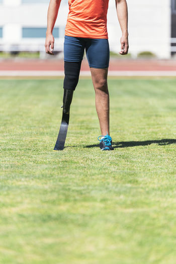Low section of athlete with prosthetic leg standing on field