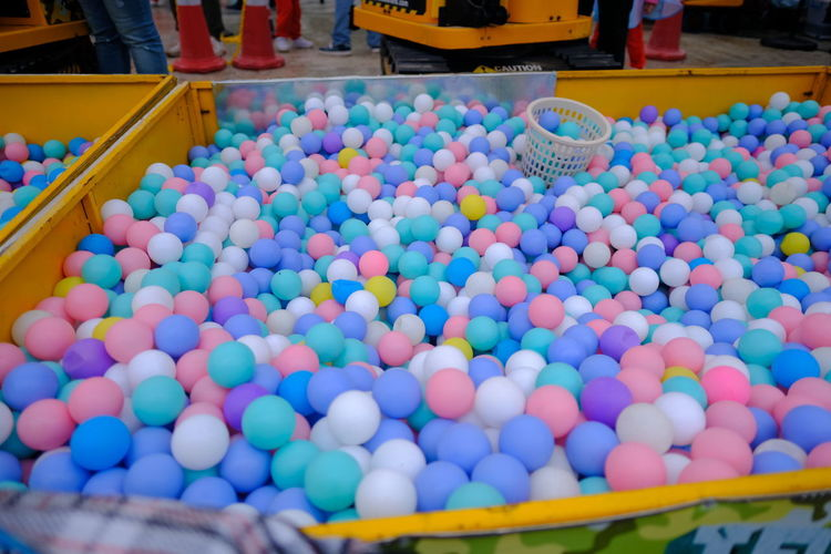 High angle view of multi colored balls in crate