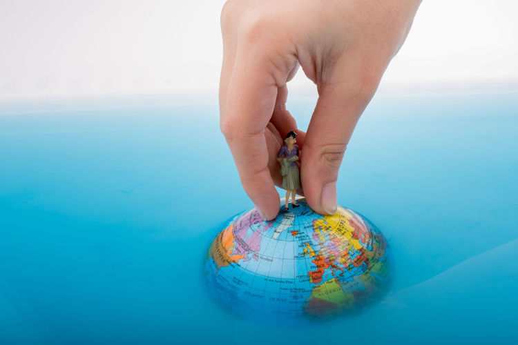 Close-up of woman hand holding globe with figurine in water