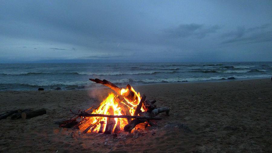 Bonfire on beach against sky