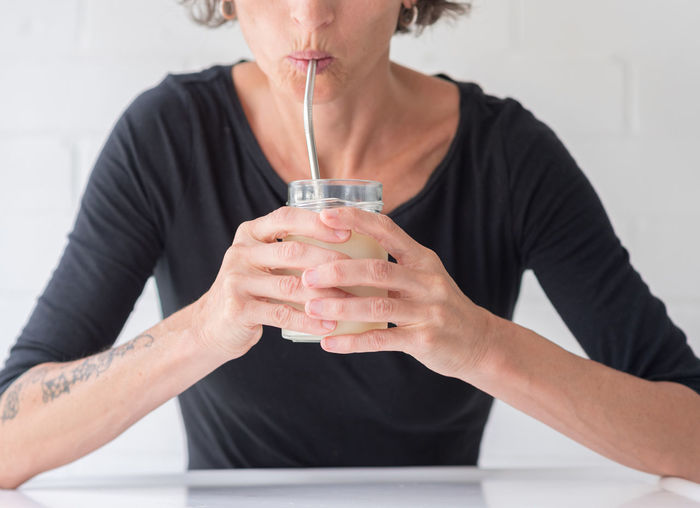 Woman drinking milk through metal straw Front View One Person Holding Drink Indoors  Refreshment Adult Lifestyles Real People Women Casual Clothing Food And Drink Glass Mature Adult Focus On Foreground Household Equipment Midsection Drinking