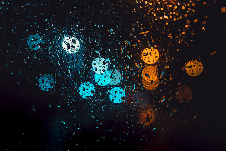 Full frame shot of water drops on illuminated glass