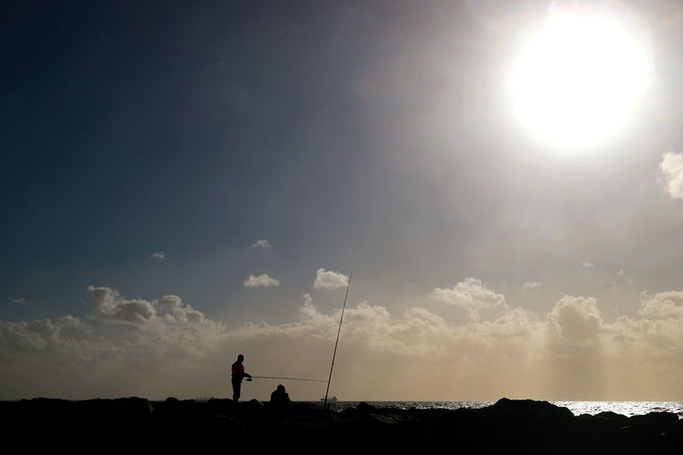 Fishing Sky Standing Real People Sunlight Men One Person Nature Beauty In Nature Cloud - Sky Silhouette Lifestyles Land Leisure Activity Sun Tranquility Environment Lens Flare Scenics - Nature Tranquil Scene Outdoors Bright Fishing