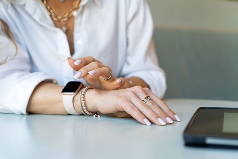 Midsection of woman using smart phone on table