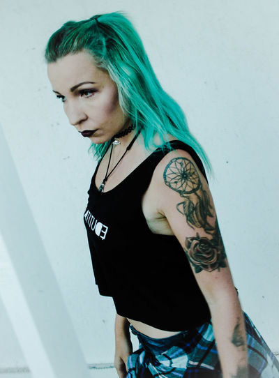 Stylish woman with tattoo standing against white wall