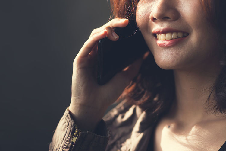 Close-up portrait of smiling young woman against black background