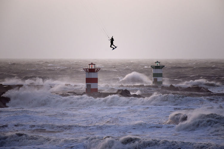 Person kiteboarding on sea against clear sky