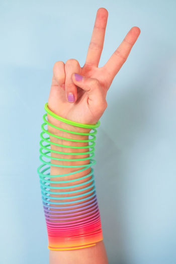 Cropped image of hand wearing spiral bracelet against colored background