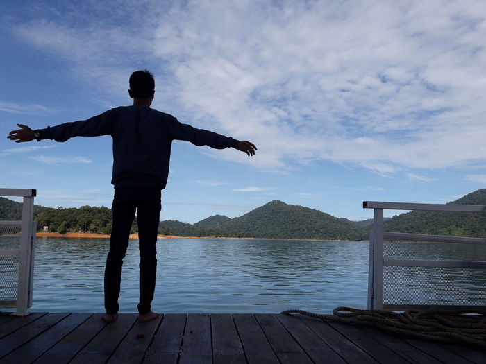 Rear view of man with arms outstretched standing on pier over lake against sky
