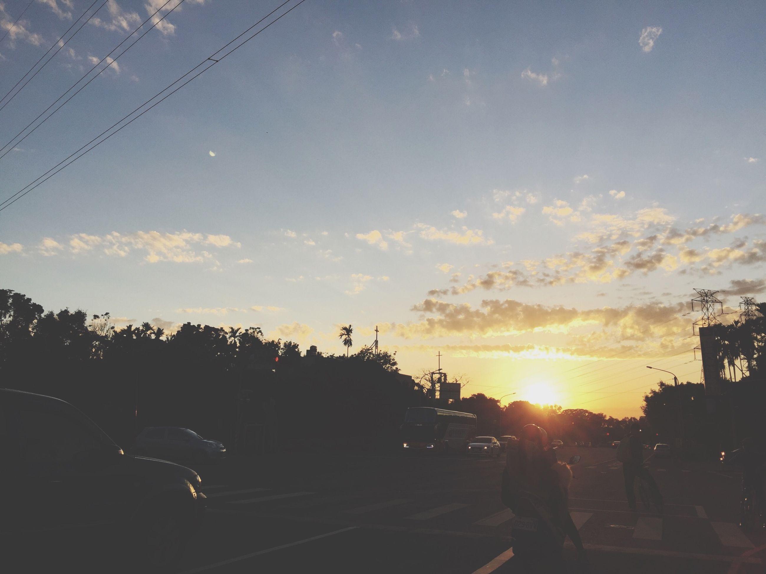 sunset, sky, transportation, car, land vehicle, sun, silhouette, mode of transport, street, cloud - sky, sunlight, tree, road, city, outdoors, building exterior, large group of people, sunbeam, nature