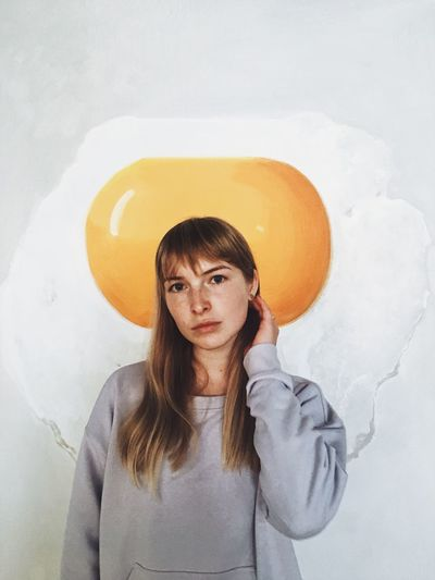 Portrait Of Young Woman Standing Against Fried Egg Poster On Wall