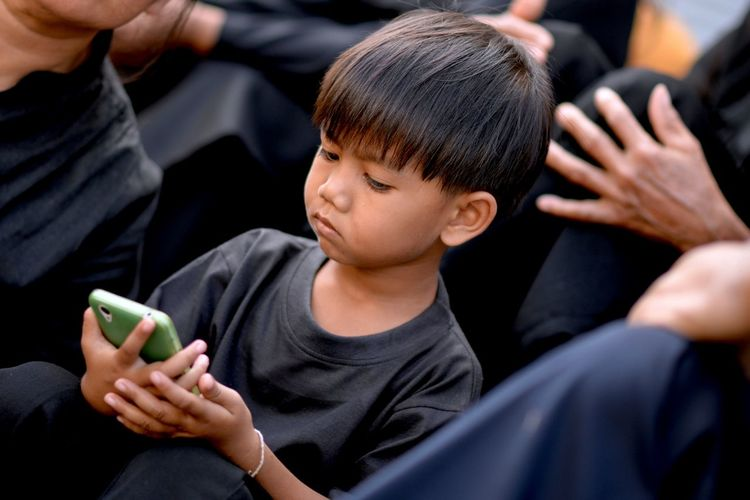 Close-up of boy using mobile phone