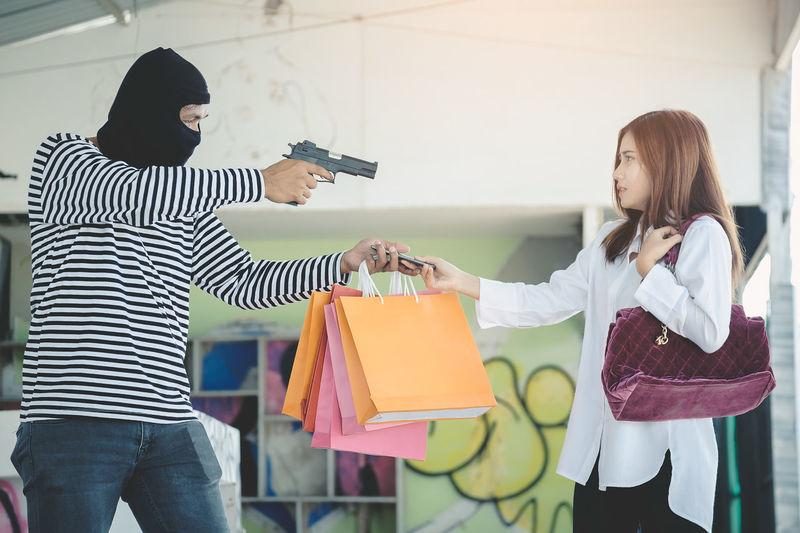 Burglar showing gun to woman giving shopping bags