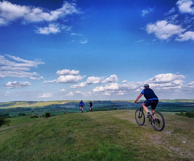 Mountain Bike Adventures Bicycle Sky Cloud - Sky Adventure Cycling Grass Nature Men Mountain Bike Two People Landscape Cycling Helmet Day Transportation Outdoors Leisure Activity Sport Scenics Full Length Beauty In Nature Unrecognizable Person Clouds