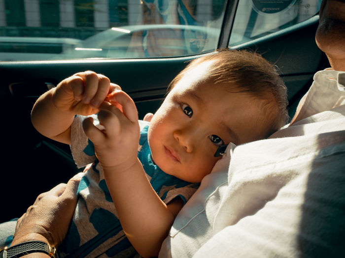 Portrait of cute baby relaxing with father in car
