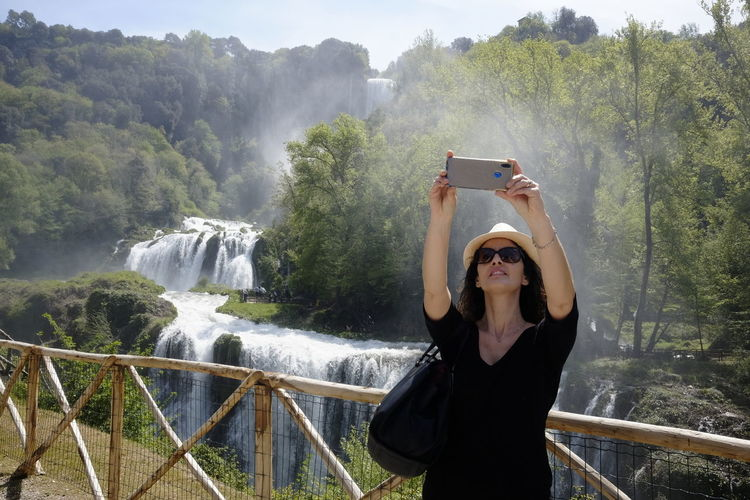 Real People Photography Themes Plant Waterfall Leisure Activity Tree Wireless Technology Technology Young Adult Communication One Person Lifestyles Water Nature Connection Standing Young Women Scenics - Nature Beauty In Nature Flowing Water Human Arm Outdoors Arms Raised Selfie