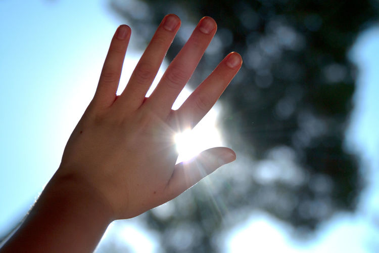Low angle view of human hand against bright sun
