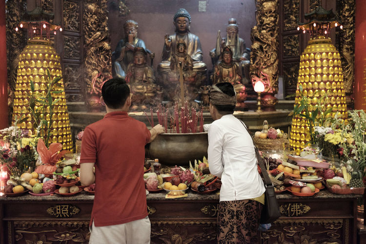 Benoa, Bali, Indonesia - January 28, 2017 : People praying and wishing a happy chinese new year on vihara satya dharma. Architecture Art And Craft Belief Built Structure Choice Creativity For Sale Human Representation Male Likeness Market Place Of Worship Real People Religion Representation Retail  Retail Display Sculpture Spirituality Statue Variation