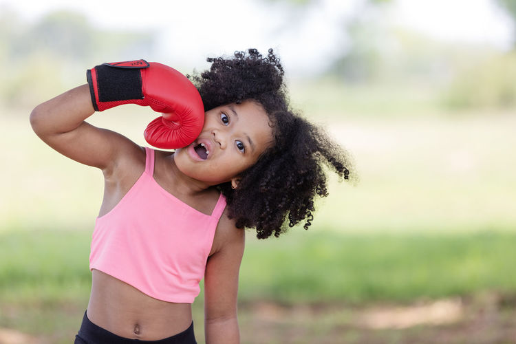 Girl punching self with boxing glove