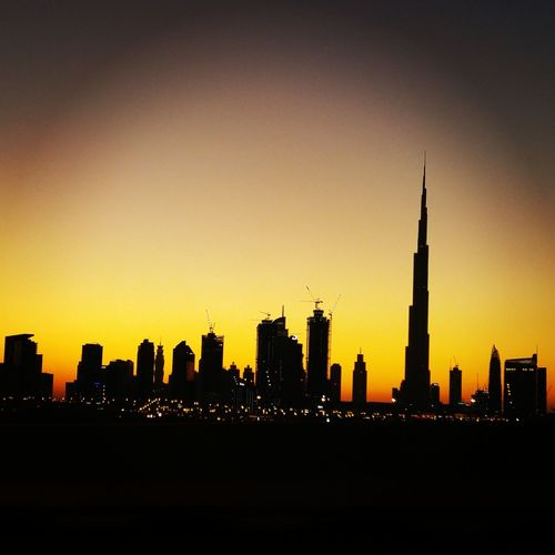 Silhouette Burj Khalifa Amidst Buildings Against Sky At Sunset