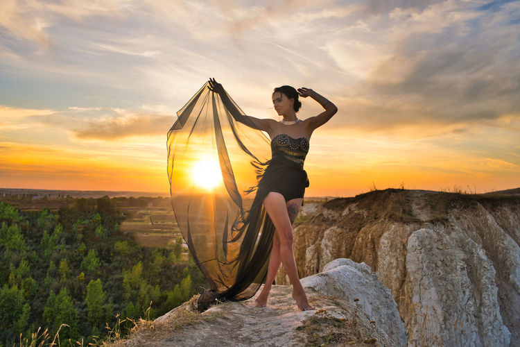 Young woman standing on rock against sky during sunset