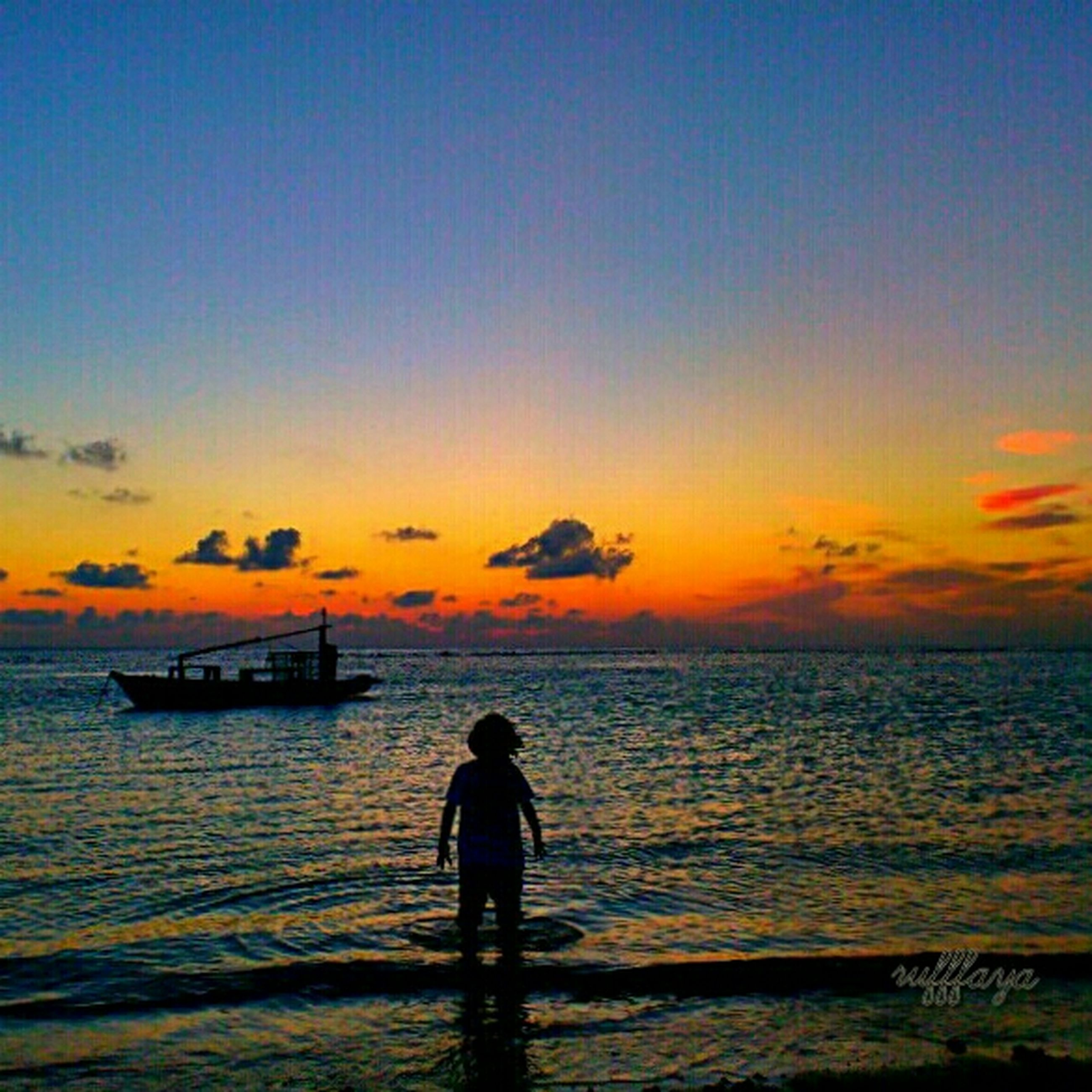 sea, water, sunset, horizon over water, beach, leisure activity, scenics, lifestyles, tranquil scene, sky, standing, tranquility, beauty in nature, silhouette, rear view, orange color, shore, idyllic